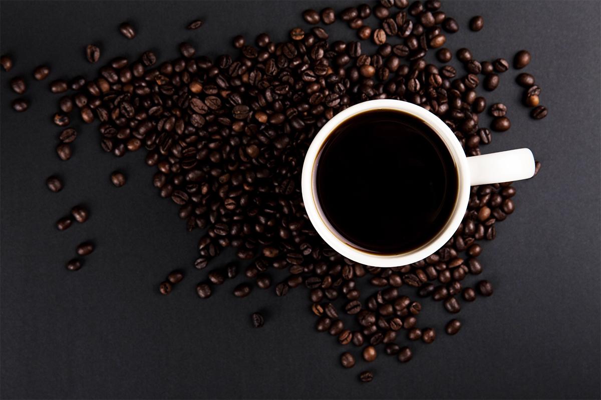 黒い机の上に乗ったコーヒーが入った白いカップ
